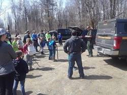 Cub Scout troops standing around listening to a Forest Ranger giving instructions on the cleanup efforts