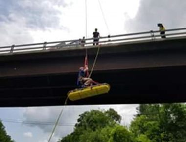 Forest Rangers practicing rope training and extraction off the side of a bridge