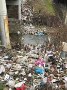 Garbage and debris spread out on the ground, down an embankment and into a stream.