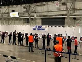 Young students lined up in a row in a large room, all aiming with bows at targets
