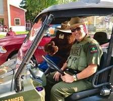 Forest Ranger John Kennedy and Smokey Bear in an automobile
