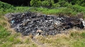 A large, charred area of grass and brush that has been burned