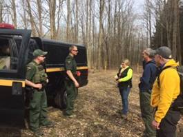 Forest Rangers and Chautauqua Area Search Team members standing in the woods getting instructions on land navigation.