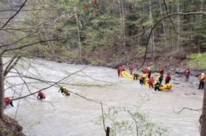 Forest Rangers with two yellow rafts in a river, rescuing disoriented hikers